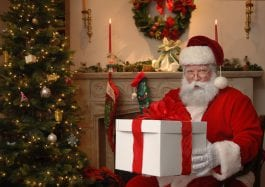 Santa next to a Christmas tree giving a gift